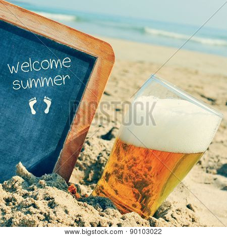 closeup of a glass of refreshing beer and a chalkboard with a wooden frame and the text welcome summer written in it, placed on the sand of a beach