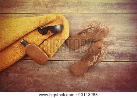 Vacation Concept. Orange towel and beach items on wood background
