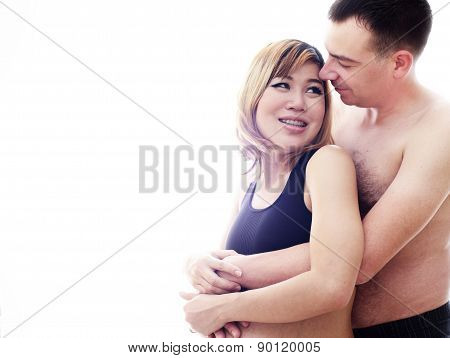 Beautiful future parents: his pregnant asian wife and a happy husband acting hug together