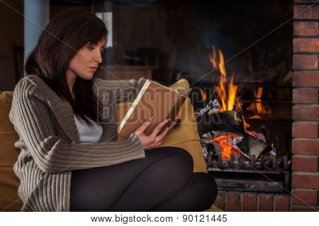 Woman Reading A Book By Fireplace