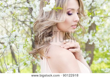 beautiful cute tender young blonde girl in a garden of flowering trees in gentle tones