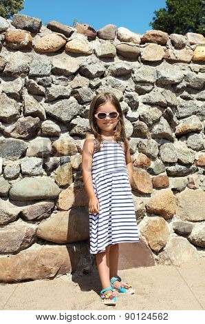 Summer, Vacation, Travel And People Concept - Little Girl Child In Striped Dress Against The Stone W