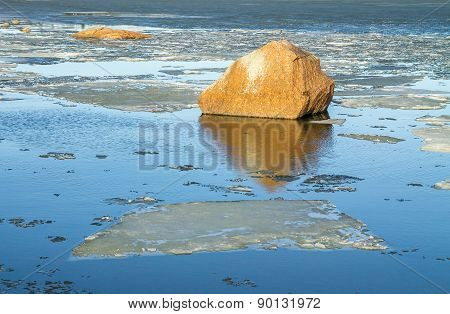 Rock Reflecting In The Icy Spring Ocean