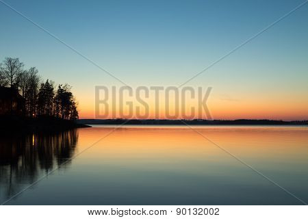 Cabin On The Point Reflecting In The Lake With Spring Sunset Colors