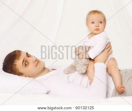 Father And Baby At Home Lying On The Bed Together, Child Playing With Teddy Bear Toy