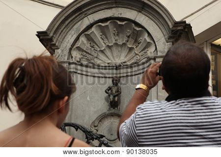 BRUSSELS, BELGIUM - AUGUST 13, 2012: Tourists look at the Manneken Pis in Brussels, Belgium.