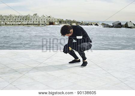 Man runner taking a break during training outdoors in seaside landscape.