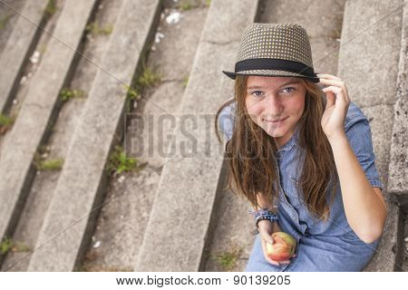 Cute young girl sitting on the stone steps, top view, looking at the camera.