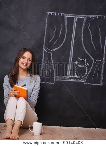 Young woman sitting on the floor near dark wall with painted a window
