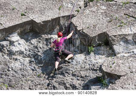Woman Climbing A Vertical Rock Along River Meuse In Belgium