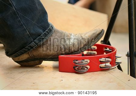 Musician Are Using A Foot Knocked Tambourine