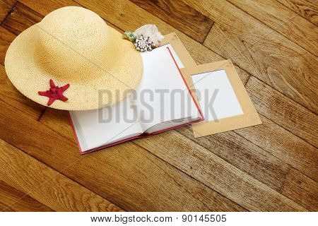 Straw Hat With Book And Red Starfish On Shabby Wooden Background