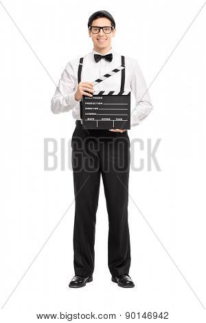 Full length portrait of a young movie director holding a movie clapperboard, smiling and looking at the camera isolated on white background