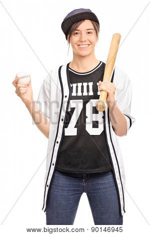 Vertical shot of a cheerful young girl holding a baseball bat and a ball and looking at the camera isolated on white background