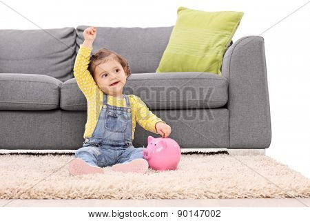 Studio shot of a cute little girl putting money into a piggybank seated on the floor in front of a modern gray sofa isolated on white background