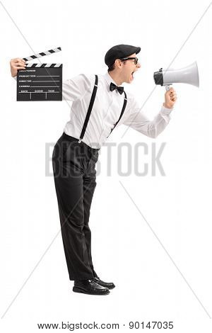 Full length profile shot of a young movie director holding a clapperboard and shouting on a megaphone isolated on white background