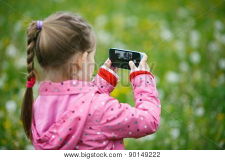 Little Girl Exploring Nature With Her Smartphone
