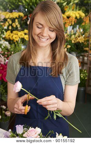 Florist Working On Flower Arrangement In Shop