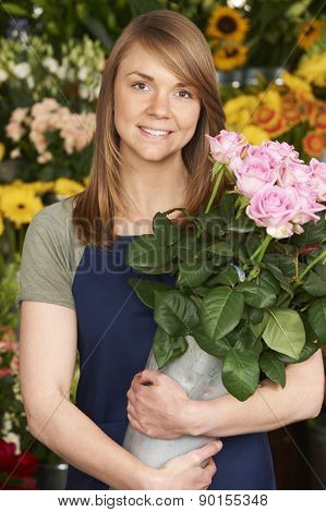 Portrait Of Florist In Shop Holding Bucket Of Roses