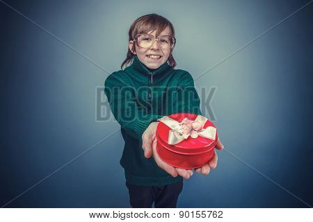European-looking boy of ten years  in glasses holding  a gift bo