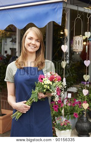 Florist Standing Outside Florist Shop With Bouquet