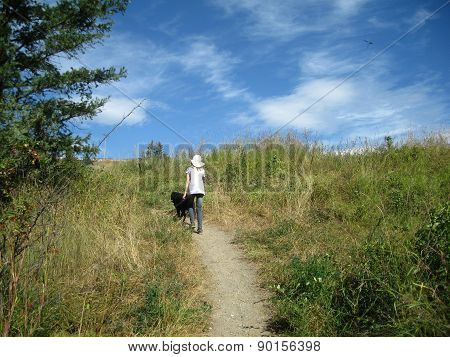 Girl hiking in the country with her dog