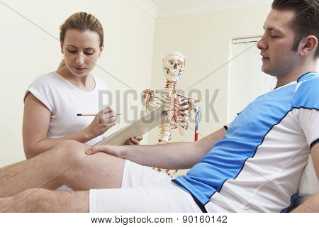 Male Patient Describing Sports Injury To Osteopath