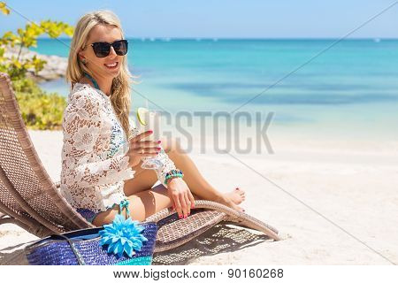 Woman drinking cocktail and relaxing in chair on the beach