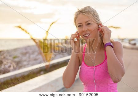 Woman listening to music while doing workout outdoors