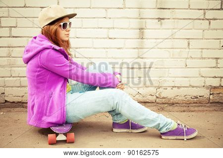 Blond Teenage Girl In Jeans Sits On Her Skateboard