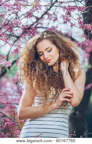 Beautiful young woman with gorgeous curly fair outdoors,flowering