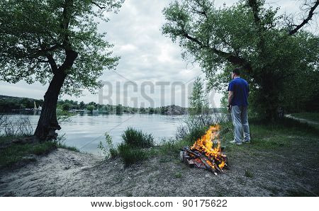 Man And Bonfire In The Spring Forest. Coals Of Fire
