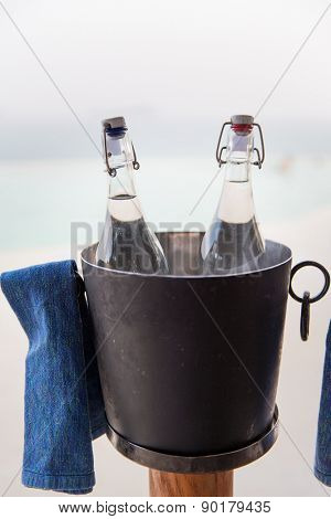 drinks, thirst, refreshment and summer resort concept - couple of water bottles in ice bucket at hotel beach