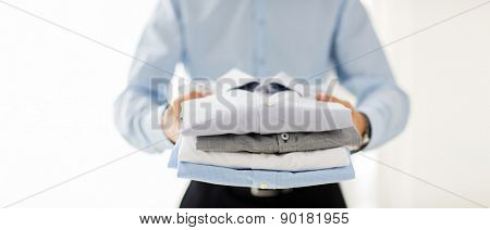 business, clothing and people concept - close up of businessman holding folded shirts