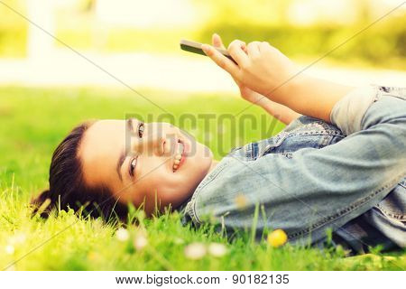 lifestyle, summer vacation, technology, leisure and people concept - smiling young girl with smartphone lying on grass in park