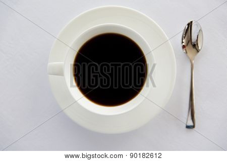 drinks, energetic, morning and caffeine concept - cup of black coffee with spoon and saucer on table