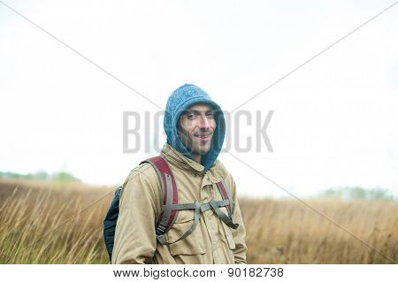 Backpacker tourist in field looking at camera