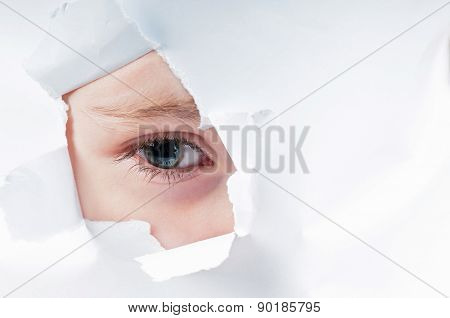 Cute baby girl looking through paper hole