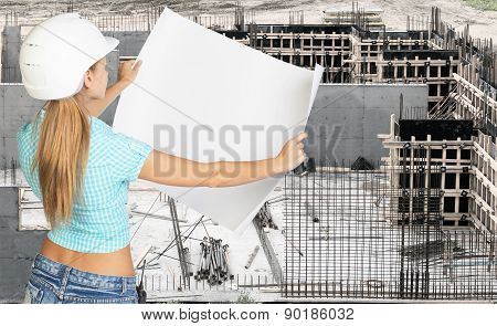 Young woman in white hard hat holding paper