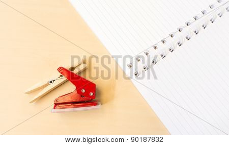 Single Red Hole Punch And Clothespin With Open White Notebook On Table Surface