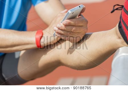 Stretching Athlete Checks Fitness Results