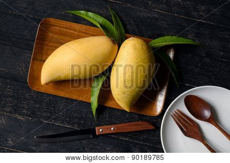 Mango And Leaves In Wood Tray With Knife And Dish On Wood Table