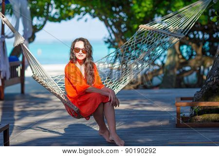 Beautiful woman relaxing on hammock during summer vacation