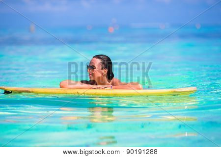 Young surfer girl surfing in turquoise sea