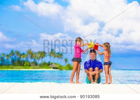 Young dad and little girls having fun during summer beach vacation