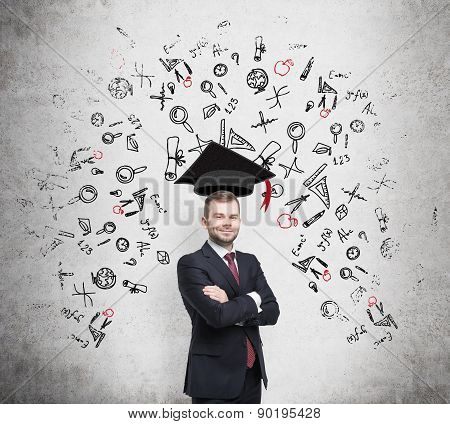 Young Handsome Businessman Is Thinking About Education At Business School. Drawn Business Icons Over
