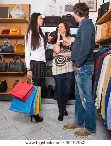 Two Young Happy Woman With Shopping Bags And Male Sales Assistant