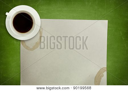 Green blackboard background with coffee cup and empty paper sheet