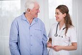 stock photo of pajamas  - Senior sick man in pajama and pretty smiling nurse - JPG