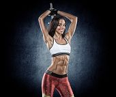 foto of tanga  - young beautiful girl with a sports figure doing exercises with dumbbells - JPG